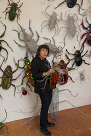 Joan Danziger surrounded by some of her work.The exhibit consists of 72 beetle sculptures. They are consisted in different shapes, sizes and mixed media such as fused glass, metal,copper and paint. In this site-specific exhibition they are climbing up 50 foot walls, ceilings and corners of the Museum.
