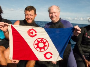 Craig Cook MN'01 and Camrin Braun FE'12 with Flag 118 immediately after surfacing from their Carondelet seamount dive. Their team was the first to ever dive this mid pacific ocean seamount.