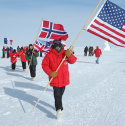 Jerry Marty carries the U.S. flag leading the procession of flags of Antarctic Treaty nations from the old to the new South Pole Station on Jan. 12, 2007 for the dedication of the new station. National Science Foundation photo by Glenn Grant.